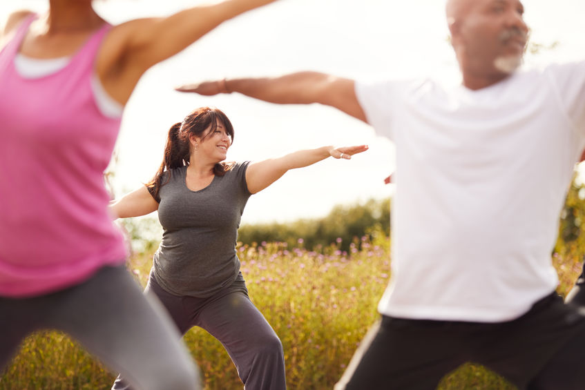 diverse people practicing yoga, tai chi, and qigong outside