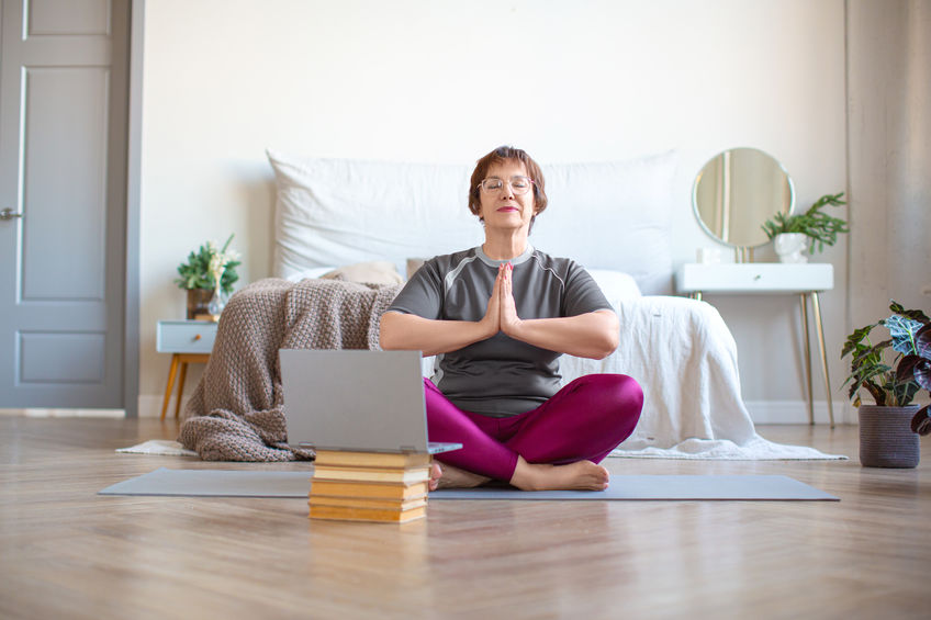 middle age white woman taking an online yoga class