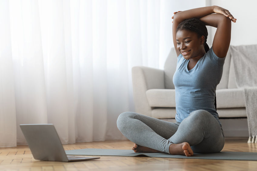 young black woman taking an online yoga class