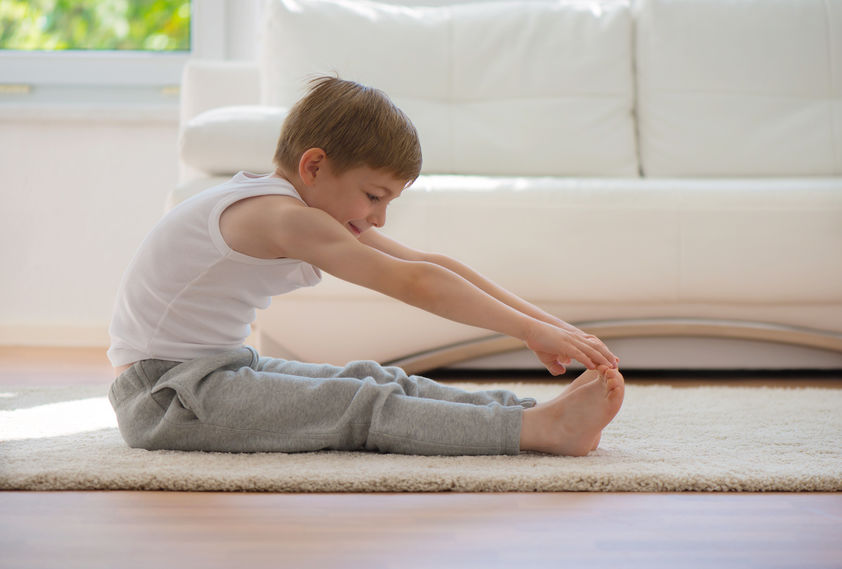 young boy doing yoga and meditation at home