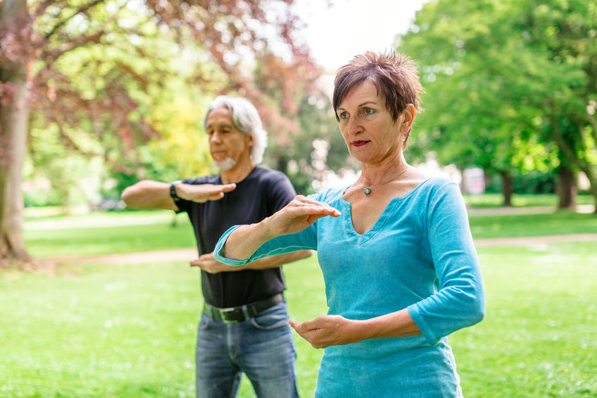 Woman and man doing tai chi in a park