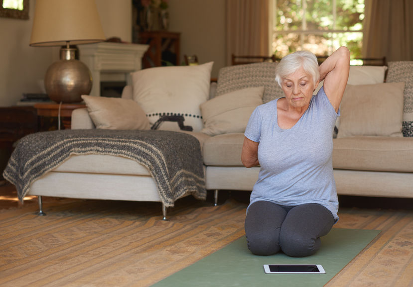 Senior woman taking an online yoga class