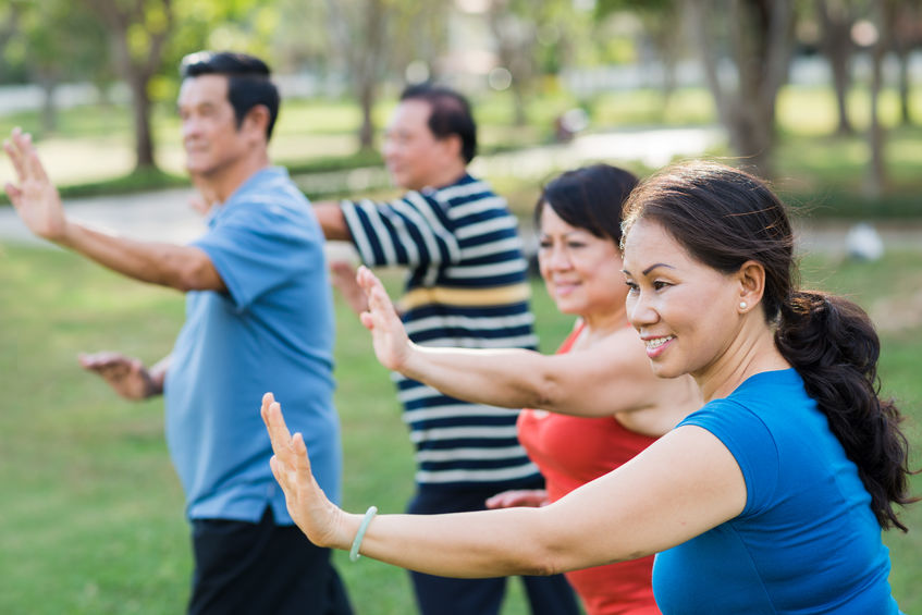 Asian family doing tai chi outside
